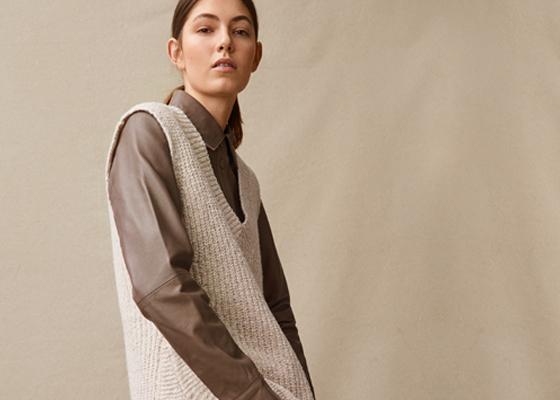 Weibliches Model in weißer Strickjacke und dunkelbraunem Kragenhemd