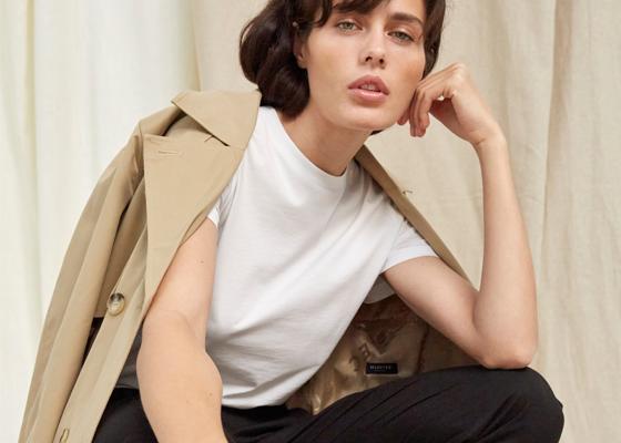 Weibliches Model mit beigem Trenchcoat weißes Oberteil und schwarzer Hose