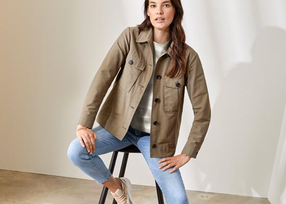 Weibliches Modell mit beiger Stoffjacke Jeans auf Barhocker