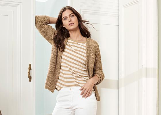 Weibliches Model in beiger Strickjacke weiß beige gestreiftem Oberteil und weißer Hose
