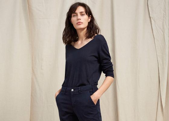 Weibliches Model in schwarzem Oberteil und schwarzer Hose