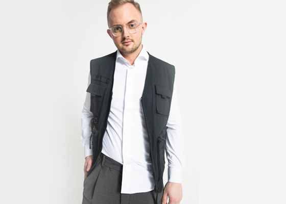 Männliches Model mit schwarzer Weste weißem Kragenhemd und dunkelgrauer Hose