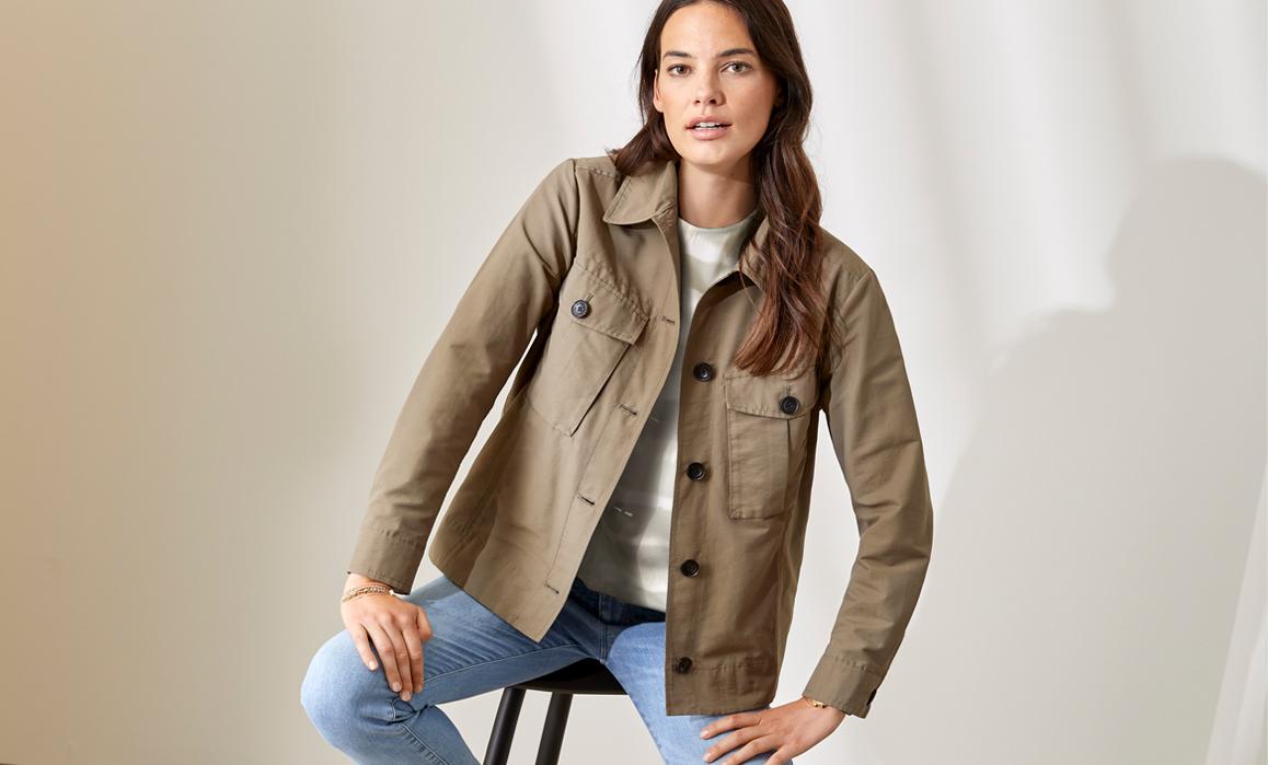 Weibliches Model posiert in brauner Stoffjacke Jeans auf Barhocker