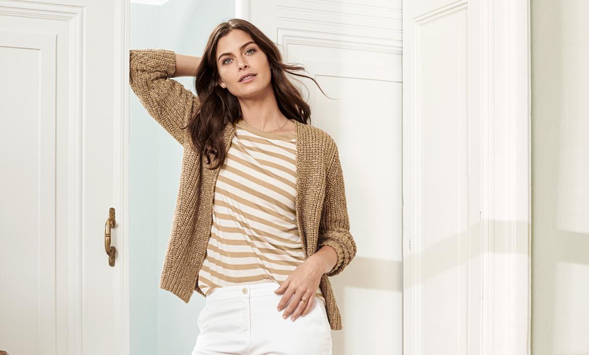 Frau posiert in moderner Freizeitkleidung vor weißen holzvertäfelten Wänden
