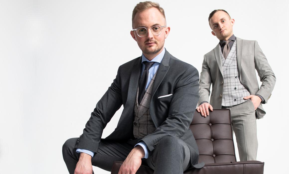 Zwei Männer in stilvoller Kleidung mit Lederstuhl vor weißem Hintergrund