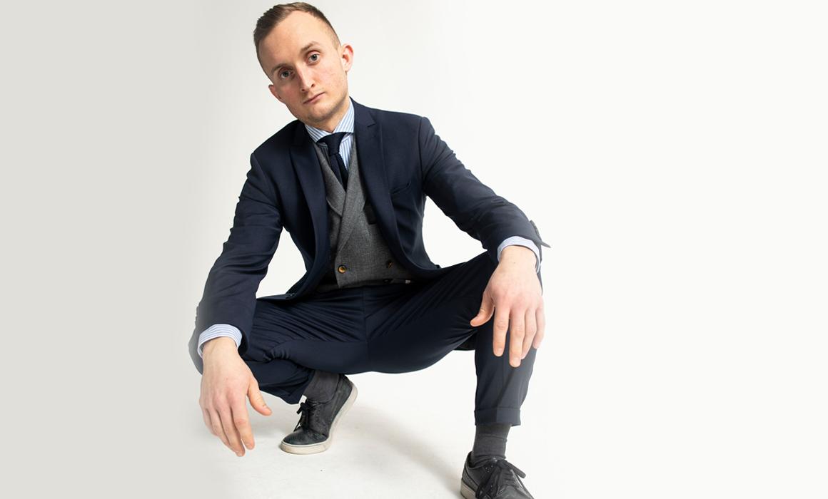 Männliches Model posiert in stilvollem Anzug in der Hocke vor weißem Hintergrund