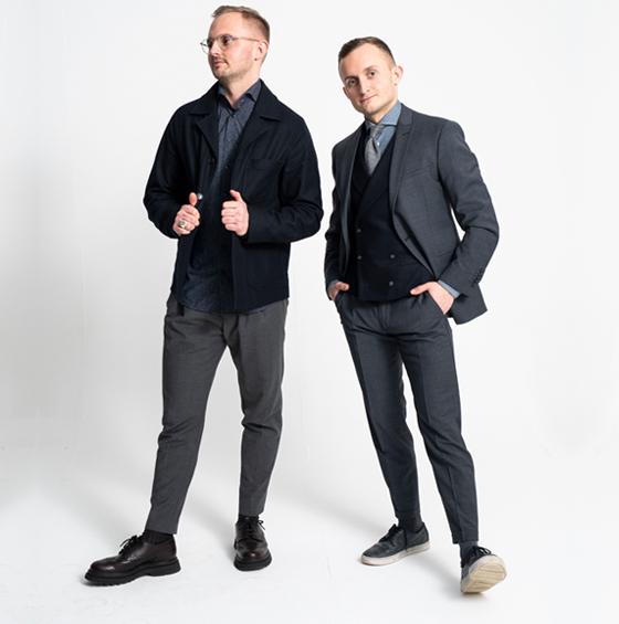 Zwei Männer in stilvoller Freizeit- und Bürokleidung vor weißem Hintergrund